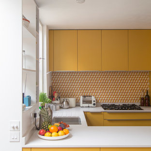 This is an example of a small contemporary u-shaped open plan kitchen in London with flat-panel cabinets, yellow cabinets, a peninsula, an integrated sink, quartzite benchtops, multi-coloured splashback, cement tile splashback, panelled appliances and dark hardwood floors.
