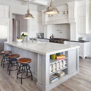 フェニックスの大きいトラディショナルスタイルのおしゃれなキッチン (アンダーカウンターシンク、落し込みパネル扉のキャビネット、白いキャビネット、クオーツストーンカウンター、白いキッチンパネル、セラミックタイルのキッチンパネル、シルバーの調理設備の、セラミックタイルの床、茶色い床) の写真