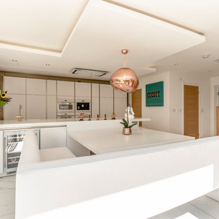 Photo of a medium sized contemporary kitchen/diner in Cheshire with flat-panel cabinets, white cabinets, white appliances, porcelain flooring, an island, white floors and white worktops.