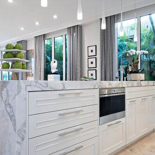 Diseño de cocina lineal, actual, grande, abierta, con salpicadero de losas de piedra, una isla, fregadero bajoencimera, armarios con rebordes decorativos, puertas de armario blancas, encimera de mármol, salpicadero blanco, electrodomésticos con paneles y suelo de piedra caliza