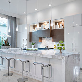 На фото: большая линейная кухня-гостиная в современном стиле с врезной раковиной, плоскими фасадами, белыми фасадами, мраморной столешницей, белым фартуком, фартуком из каменной плиты, техникой под мебельный фасад, полом из известняка и островом с