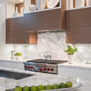 ニューヨークの広いコンテンポラリースタイルのおしゃれなキッチン (フラットパネル扉のキャビネット、大理石カウンター、白いキッチンパネル、石スラブのキッチンパネル、アンダーカウンターシンク、白いキャビネット、パネルと同色の調理設備、ライムストーンの床) の写真