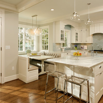 Elegant eat-in kitchen photo in DC Metro with a farmhouse sink, shaker cabinets, white cabinets, quartzite countertops, blue backsplash, glass tile backsplash and stainless steel appliances