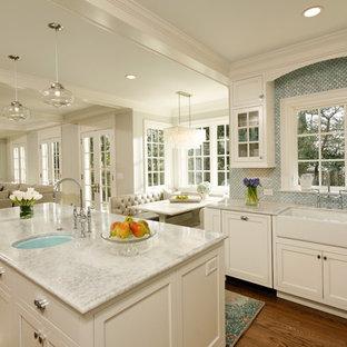 Imagen de cocina tradicional, abierta, con fregadero sobremueble, salpicadero azul, armarios tipo vitrina, puertas de armario blancas y encimera de cuarcita