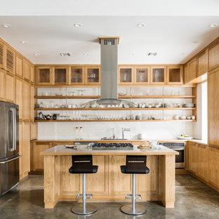 ヒューストンの中サイズのインダストリアルスタイルのおしゃれなアイランドキッチン (シェーカースタイル扉のキャビネット、中間色木目調キャビネット、ステンレスカウンター、白いキッチンパネル、セラミックタイルのキッチンパネル、シルバーの調理設備の、コンクリートの床) の写真