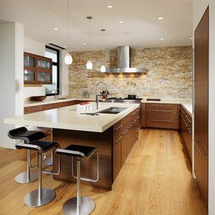 オレンジカウンティの中サイズのコンテンポラリースタイルのおしゃれなキッチン (アンダーカウンターシンク、フラットパネル扉のキャビネット、濃色木目調キャビネット、ベージュキッチンパネル、石タイルのキッチンパネル、パネルと同色の調理設備、淡色無垢フローリング、ベージュの床) の写真
