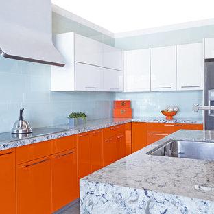 サンフランシスコの中サイズのコンテンポラリースタイルのおしゃれなキッチン (ドロップインシンク、フラットパネル扉のキャビネット、オレンジのキャビネット、大理石カウンター、青いキッチンパネル、シルバーの調理設備の) の写真