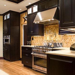Idéer för att renovera ett vintage kök, med en undermonterad diskho, luckor med upphöjd panel, skåp i mörkt trä, bänkskiva i kvarts, gult stänkskydd och rostfria vitvaror
