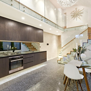 Contemporary single-wall eat-in kitchen in Sydney with a drop-in sink, flat-panel cabinets, dark wood cabinets, mirror splashback, stainless steel appliances and no island.