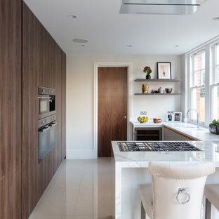 Design ideas for a contemporary u-shaped kitchen in London with flat-panel cabinets, dark wood cabinets, a breakfast bar, grey floors and white worktops.