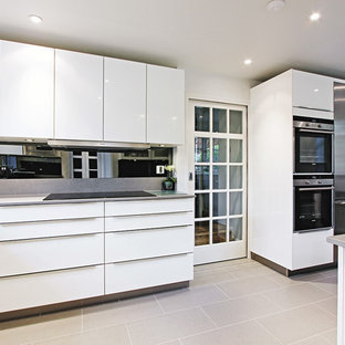 Design ideas for a contemporary kitchen in London with stainless steel appliances and grey floors.