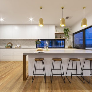 Photo of a mid-sized contemporary l-shaped kitchen in Canberra - Queanbeyan with ceramic splashback, medium hardwood floors, an undermount sink, flat-panel cabinets, white cabinets, grey splashback, black appliances, brown floor and grey benchtop.