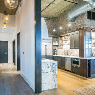 デンバーの中サイズのインダストリアルスタイルのおしゃれなキッチン (シングルシンク、落し込みパネル扉のキャビネット、濃色木目調キャビネット、大理石カウンター、マルチカラーのキッチンパネル、レンガのキッチンパネル、シルバーの調理設備の、無垢フローリング、アイランドなし、グレーの床) の写真