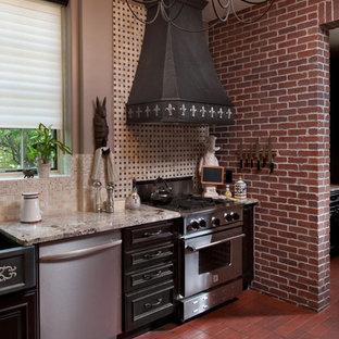 デンバーの中サイズのカントリー風おしゃれなI型キッチン (エプロンフロントシンク、落し込みパネル扉のキャビネット、黒いキャビネット、御影石カウンター、マルチカラーのキッチンパネル、モザイクタイルのキッチンパネル、シルバーの調理設備の、テラコッタタイルの床、赤い床、グレーのキッチンカウンター) の写真
