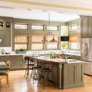 Klassisk inredning av ett stort vit vitt kök, med gröna skåp, vitt stänkskydd, rostfria vitvaror, ljust trägolv, en köksö, en undermonterad diskho, luckor med infälld panel och beiget golv