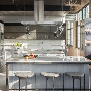 Industrial kitchen in Denver with an undermount sink, white splashback, stainless steel appliances, light hardwood floors and multiple islands.
