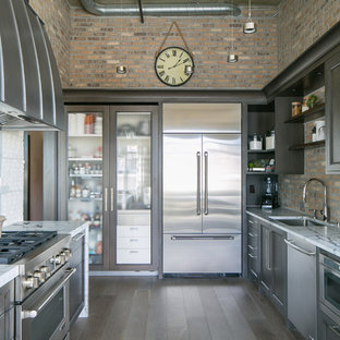 This is an example of a medium sized urban u-shaped kitchen/diner in Denver with a submerged sink, quartz worktops, stainless steel appliances, medium hardwood flooring, no island, grey floors, recessed-panel cabinets, dark wood cabinets and brown splashback.
