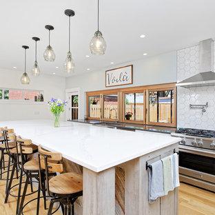 Ejemplo de cocina campestre con fregadero sobremueble, armarios estilo shaker, puertas de armario blancas, salpicadero blanco, electrodomésticos de acero inoxidable, suelo de madera clara, una isla y encimeras grises