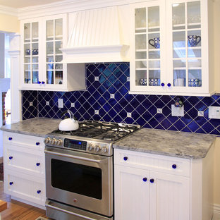 Example of a classic kitchen design in New York with glass-front cabinets and stainless steel appliances