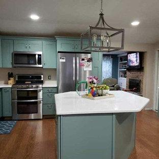 Inredning av ett eklektiskt stort vit vitt kök, med en undermonterad diskho, luckor med infälld panel, blå skåp, bänkskiva i koppar, rostfria vitvaror, ljust trägolv, en köksö och gult golv