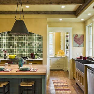Rustic kitchen designs - Inspiration for a rustic kitchen remodel in Burlington with a farmhouse sink, wood countertops, recessed-panel cabinets, yellow cabinets and green backsplash
