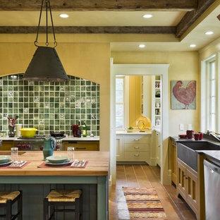 バーリントンのラスティックスタイルのおしゃれなキッチン (エプロンフロントシンク、木材カウンター、落し込みパネル扉のキャビネット、黄色いキャビネット、緑のキッチンパネル) の写真