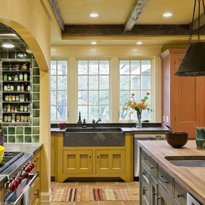 Elegant kitchen photo in Burlington with stainless steel appliances, an integrated sink, wood countertops, yellow cabinets and green backsplash