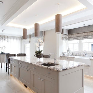 This is an example of a large traditional open plan kitchen in Other with an integrated sink, beaded cabinets, grey cabinets, granite worktops, beige splashback, metro tiled splashback, integrated appliances, ceramic flooring and an island.