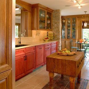 Immagine di una cucina abitabile classica con lavello sottopiano, ante di vetro, ante in legno scuro, top in pietra calcarea, paraspruzzi beige, isola, paraspruzzi in lastra di pietra, elettrodomestici in acciaio inossidabile e pavimento in travertino