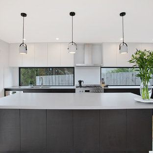 This is an example of a large contemporary single-wall kitchen in Other with an undermount sink, flat-panel cabinets, black cabinets, quartz benchtops, stainless steel appliances, with island, beige floor, window splashback and light hardwood floors.