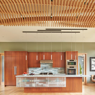 Design ideas for a mid-sized modern galley open plan kitchen in Seattle with an undermount sink, flat-panel cabinets, medium wood cabinets, recycled glass benchtops, grey splashback, glass tile splashback, stainless steel appliances, light hardwood floors and with island.