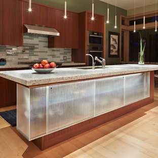 This is an example of a mid-sized modern galley open plan kitchen in Seattle with an undermount sink, flat-panel cabinets, medium wood cabinets, recycled glass benchtops, grey splashback, glass tile splashback, stainless steel appliances, light hardwood floors and with island.