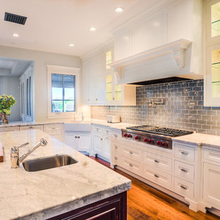 Transitional eat-in kitchen ideas - Example of a transitional l-shaped eat-in kitchen design in Phoenix with a farmhouse sink, white cabinets, marble countertops, gray backsplash, glass tile backsplash and stainless steel appliances