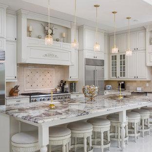 Diseño de cocina en L, clásica, con fregadero bajoencimera, armarios con paneles con relieve, puertas de armario blancas, electrodomésticos de acero inoxidable, una isla, suelo blanco y salpicadero beige