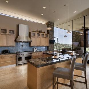 フェニックスの広いサンタフェスタイルのおしゃれなキッチン (シルバーの調理設備、シェーカースタイル扉のキャビネット、中間色木目調キャビネット、御影石カウンター、青いキッチンパネル、アンダーカウンターシンク、ガラスタイルのキッチンパネル、トラバーチンの床、ベージュの床) の写真