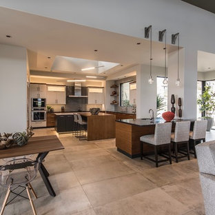 Inspiration for a large contemporary u-shaped eat-in kitchen in Phoenix with flat-panel cabinets, multiple islands, an undermount sink, dark wood cabinets, solid surface benchtops, grey splashback, glass tile splashback, panelled appliances, cement tiles, grey floor and black benchtop.