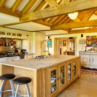 Photo of an expansive traditional eat-in kitchen in Berkshire with a drop-in sink, glass-front cabinets, limestone benchtops, grey splashback, mirror splashback, panelled appliances, limestone floors and with island.