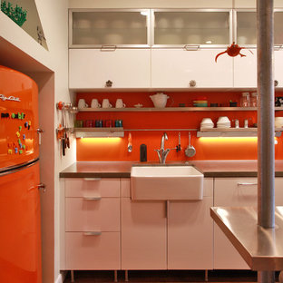 This is an example of an industrial kitchen in DC Metro with a farmhouse sink, concrete benchtops, coloured appliances, flat-panel cabinets, white cabinets and orange splashback.