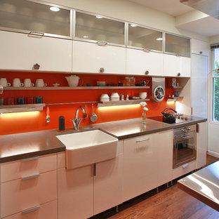 Inredning av ett industriellt kök, med en rustik diskho, rostfria vitvaror, släta luckor, vita skåp och orange stänkskydd