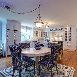 Große Klassische Wohnküche in U-Form mit Einbauwaschbecken, Glasfronten, weißen Schränken, Arbeitsplatte aus Fliesen, Küchenrückwand in Weiß, Rückwand aus Porzellanfliesen, weißen Elektrogeräten, braunem Holzboden und Kücheninsel in Montreal