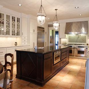 ウィチタの中くらいのトランジショナルスタイルのおしゃれなキッチン (エプロンフロントシンク、シェーカースタイル扉のキャビネット、白いキャビネット、御影石カウンター、白いキッチンパネル、サブウェイタイルのキッチンパネル、シルバーの調理設備、テラコッタタイルの床、赤い床) の写真