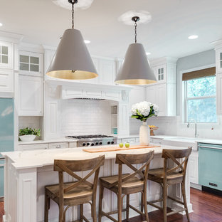 Transitional l-shaped medium tone wood floor and brown floor kitchen photo in Philadelphia with a farmhouse sink, raised-panel cabinets, white cabinets, white backsplash, subway tile backsplash, colored appliances and an island