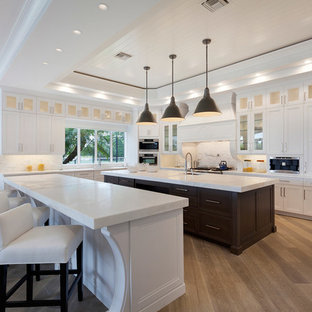 Transitional kitchen designs - Transitional u-shaped medium tone wood floor kitchen photo in Miami with recessed-panel cabinets, white cabinets, white backsplash, stainless steel appliances and two islands