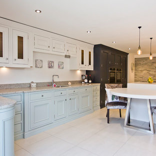 This is an example of a medium sized classic l-shaped kitchen/diner in Other with a submerged sink, recessed-panel cabinets, blue cabinets, granite worktops, stainless steel appliances, an island and beige floors.