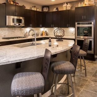 Example of a huge trendy u-shaped ceramic floor open concept kitchen design in Phoenix with an undermount sink, flat-panel cabinets, dark wood cabinets, granite countertops, beige backsplash, stone slab backsplash and stainless steel appliances