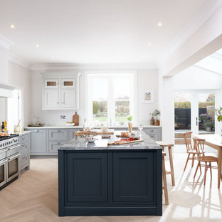 This is an example of a large classic l-shaped kitchen/diner in London with shaker cabinets, grey cabinets, white splashback, light hardwood flooring, an island, stainless steel appliances, white worktops and beige floors.