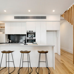 Photo of a contemporary l-shaped open plan kitchen in Sydney with black splashback, medium hardwood floors, with island, a drop-in sink, flat-panel cabinets, white cabinets, mosaic tile splashback and stainless steel appliances.