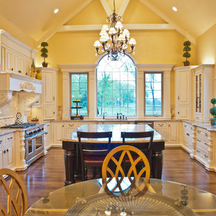 Traditional eat-in kitchen ideas - Example of a classic u-shaped eat-in kitchen design in Nashville with raised-panel cabinets, beige cabinets and paneled appliances
