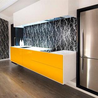 Modern inredning av ett stort linjärt kök med öppen planlösning, med en integrerad diskho, gula skåp och rostfria vitvaror