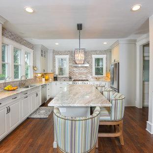 フィラデルフィアのトランジショナルスタイルのおしゃれなキッチン (アンダーカウンターシンク、レイズドパネル扉のキャビネット、白いキャビネット、グレーのキッチンパネル、レンガのキッチンパネル、シルバーの調理設備の、濃色無垢フローリング、茶色い床、ベージュのキッチンカウンター) の写真